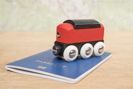 Conceptual photo of travel with train locomotive on blue passport on old wooden table on map background