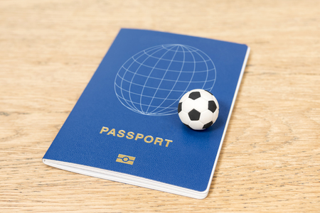 small toy soccer ball and biometric passport on a wooden table