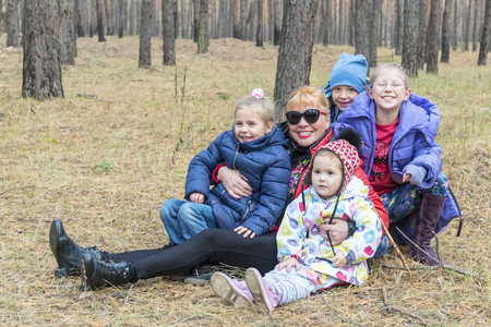 portrait of a grandmother with her grandchildren sitting on the ground in a coniferous forest