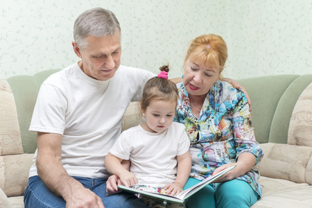 Grandmother and grandfather are reading a book to their granddaughter while sitting on the couch 写真素材