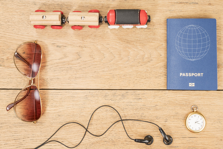 Wooden train, headphones, passport and other attributes of the traveler on the old wooden table as a background