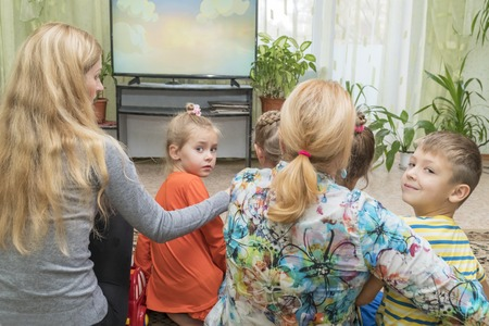 Grandmother with her daughter and grandchildren watching TV, rear view. The kids turned to the camera 写真素材