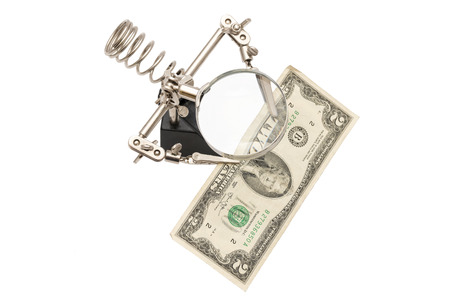 view of dollars clamped through a magnifying glass isolated on white background