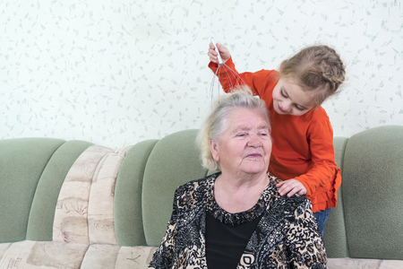 Little granddaughter gives her great-grandmother a head massage with a metal massager