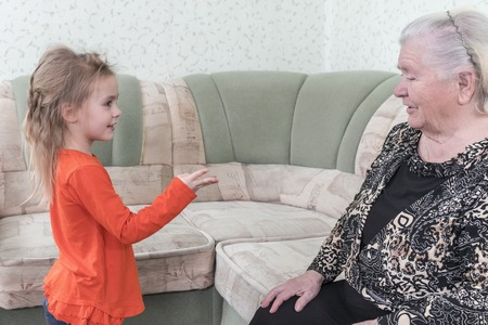 Little beautiful girl counts on his fingers, showing off her great-grandmother