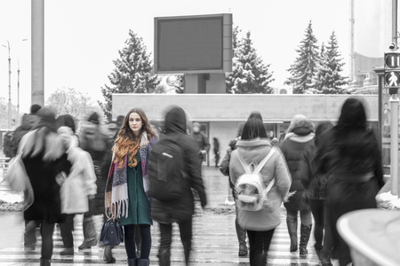 woman walking along a pedestrian crossing and standing out from the crowd