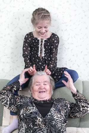 child makes the horns of his great-grandmother sitting on the back of the sofa