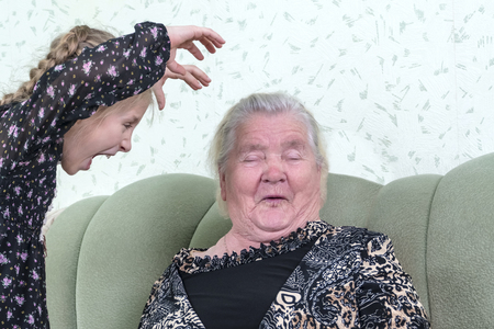 granddaughter scares grandmother making a terrible grimassu and raising his arms