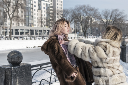 one woman in a fur coat pushes another standing at the fence of the embankment of the city river