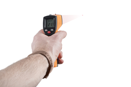 Infrared thermometer in a man hand measures the temperature, isolated on white background