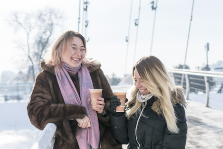 two women standing on the bridge laughing and drinking coffee with foam on their lips