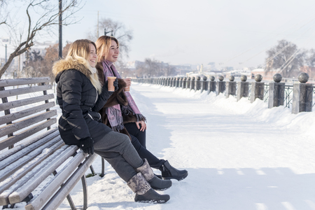 Two laughing friends sitting on a bench with a cup of coffee at the winter promenade