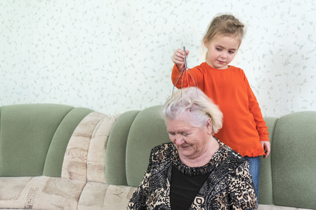 child is massaging the head of the great-grandmother with a metal massager