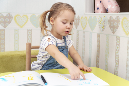 little beautiful girl points to her drawing sitting at the table in the nursery