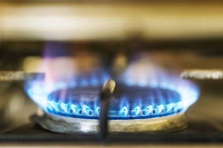 burning blue flame gas on the old stove in the kitchen Foto de archivo