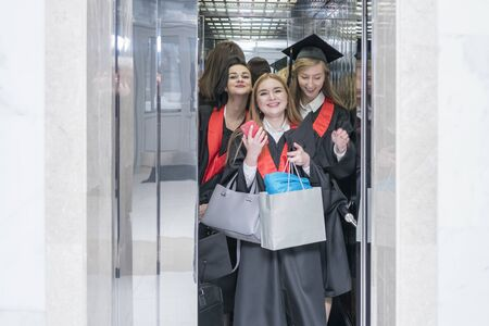 Kharkov, Ukraine - November 27, 2018: Group of cheerful female students in robes with bags in the elevator of the university Editorial