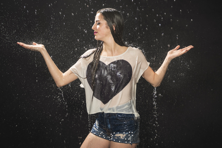 beautiful woman rejoices in the rain his arms to the side, palms up, on a black background