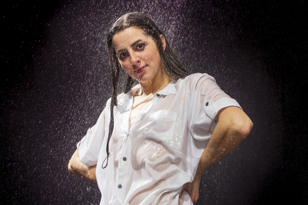 portrait of a beautiful wet sexy woman in a translucent shirt, clinging to the body, in the pouring rain on a black background