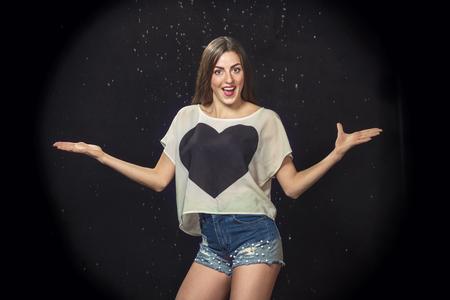 beautiful joyful woman on a black background with water drops