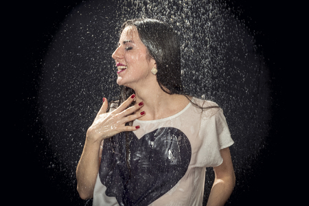 beautiful woman in a shirt with a heart is wet in the pouring rain on a black background