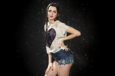 portrait of wet woman in t-shirt and shorts under water drops on black background
