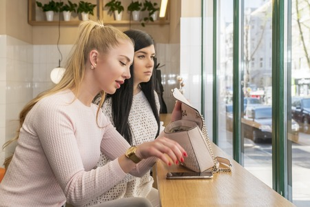 woman sitting at a table in a cafe pulls the phone out of the bag Stock Photo