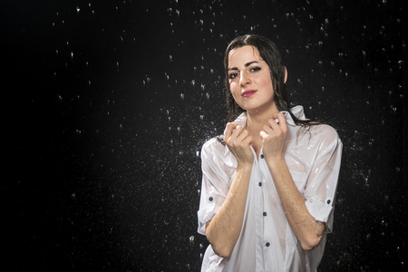 beautiful wet sexy woman holding her collar under water drops Stock Photo