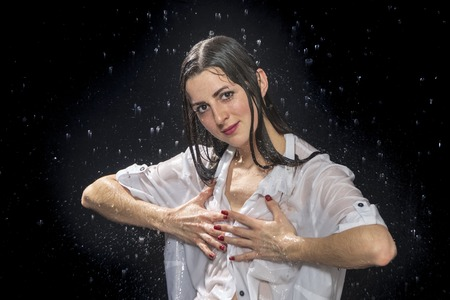 beautiful wet woman in a white shirt covers her breast, on a black background Stock Photo