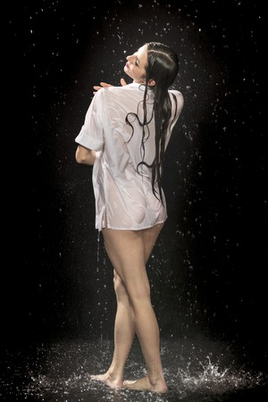 portrait of a beautiful sexy naked woman in a wet shirt stuck to her body under water drops on a black background, rear view