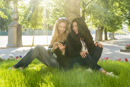 two beautiful women look into the phone with a smile while sitting on the grass by a tree