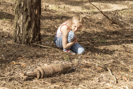 child looks curiously at the rusty unexploded bomb lying on the needles in a pine forest