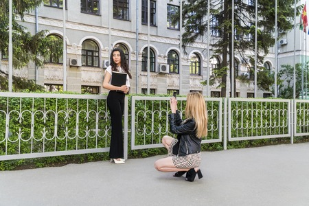 One female student photographs another at the university fence