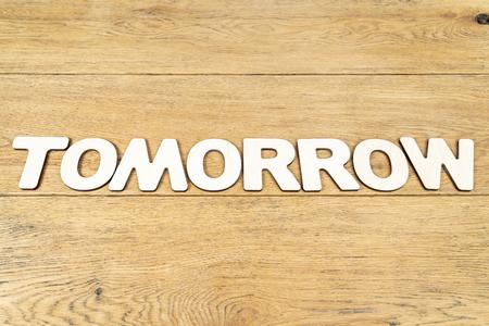 Palabra: mañana, en letras de madera sobre una vieja mesa de madera Foto de archivo