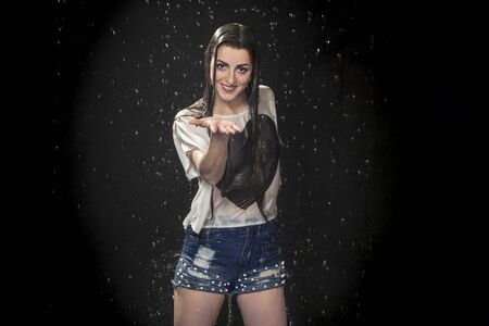 beautiful wet woman in the rain opened her palm forward, on a black background Standard-Bild
