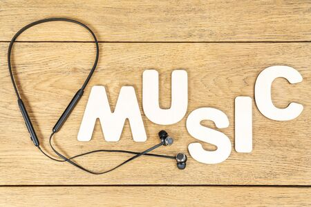 word music laid out of wooden letters next to wireless headphones on an old wooden table Stok Fotoğraf
