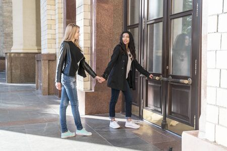 two students holding hands enter the university building
