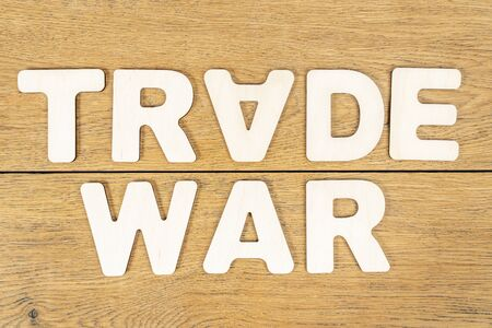 phrase - trade war, laid out letters on an old wooden oak table