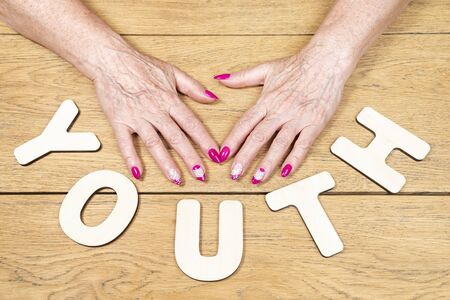 word youth, spread out of wooden letters with old female hands with a manicure