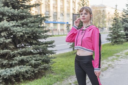 portrait of a beautiful sporty woman standing on a city street near the road with headphones in her ears