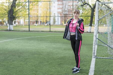 portrait of a beautiful sports woman at the football goal in the stadium Stok Fotoğraf