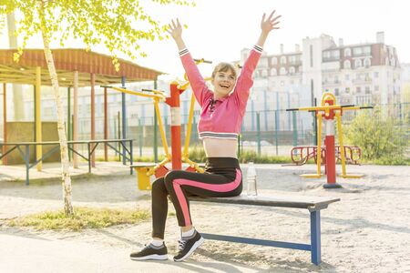 joyful athletic woman raised her hands up sitting on a bench on the sports ground in the city