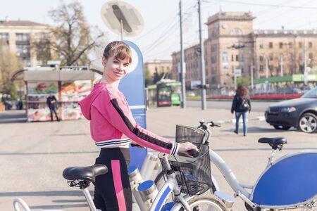 Beautiful athletic woman at the city bike rental