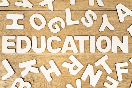 word education is laid out of wooden letters in the middle of various letters randomly scattered on a wooden table Stok Fotoğraf