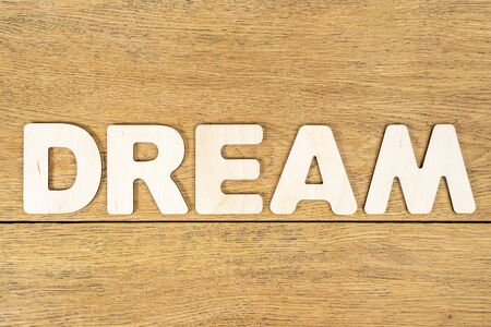 Word - dream, laid out in wooden letters on an old wooden table