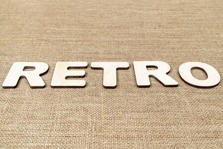 word - retro is laid out in wooden letters on the old brown sacking