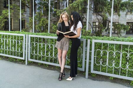 two beautiful students of different nationalities are studying a textbook, standing at the fence of the university