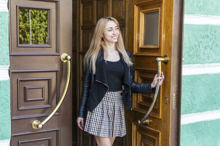 beautiful smiling blonde woman opening a large wooden door coming out of the building