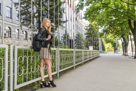 portrait of a beautiful woman with long legs with a backpack on the shoulder at the university building