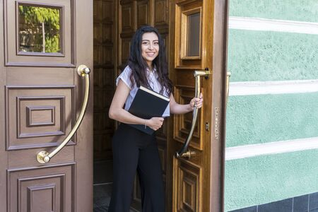 portrait of a beautiful hispanic woman with the book in hand coming out of the building through a large wooden door Stok Fotoğraf
