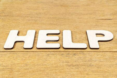 Word - help, laid out in wooden letters on an old wooden table Stok Fotoğraf